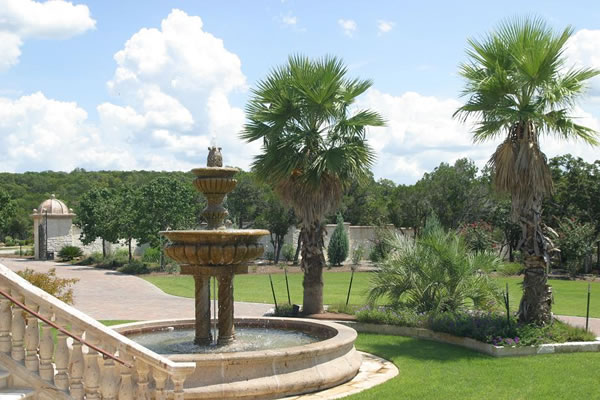 Large stone fountain designed by Oasis Gardens commands front entrance vista